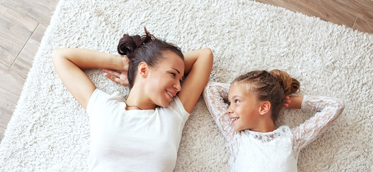 Mother and daughter wearing white tops whilst laying on a carpeted floor.